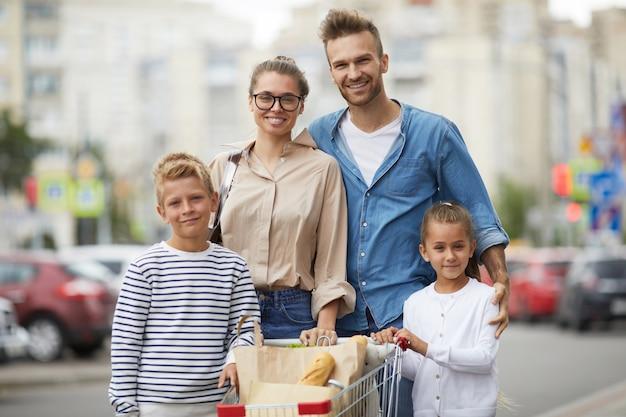 Família posando com carrinho de compras ao ar livre