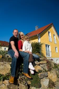 Família posando na frente de uma casa