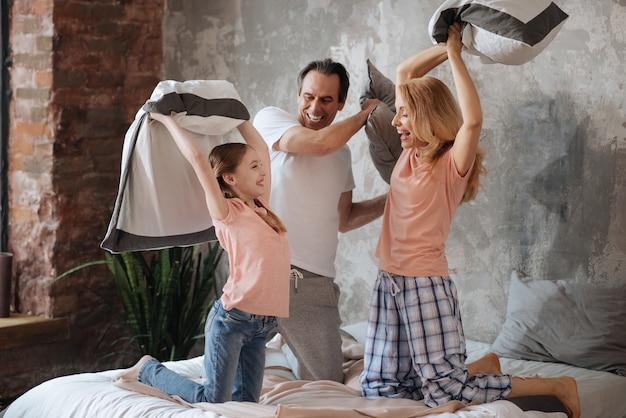 Família positiva alegre e brincalhona se divertindo em casa e se divertindo enquanto desfruta da luta de travesseiros