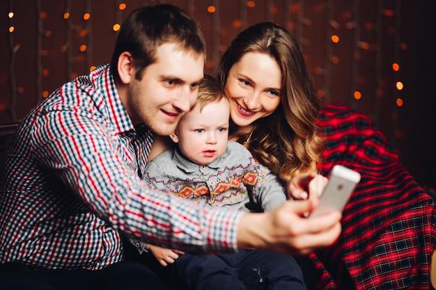 Família positiva com o filho loiro tirando foto no estúdio durante o tempo de natal.