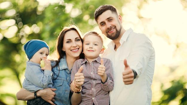 Família positiva e elegante, gesticulando com polegares para cima