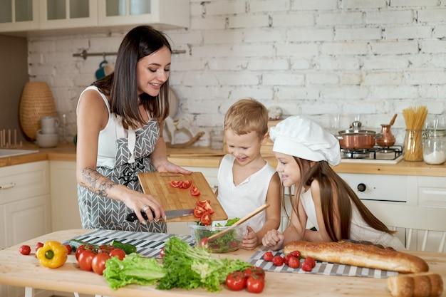 Família prepara o almoço na cozinha. a mãe ensina a filha e o filho a preparar uma salada de legumes frescos. alimentação saudável e natural, vitaminas para crianças
