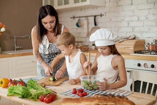 Família prepara o almoço na cozinha. a mãe ensina a filha e o filho a preparar uma salada de legumes frescos. alimentos naturais saudáveis, vitaminas para crianças