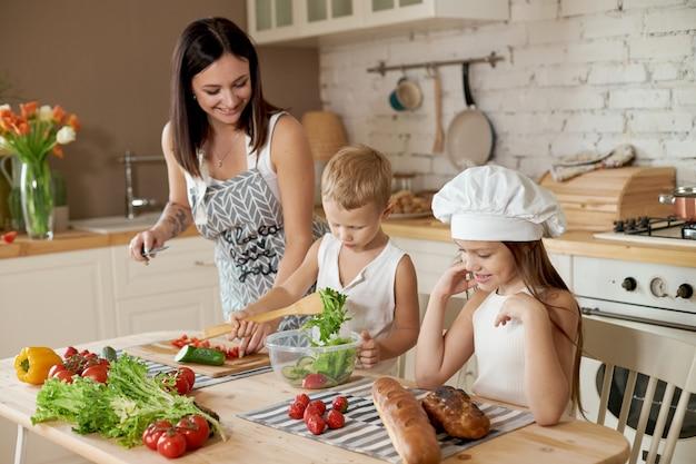 Família prepara o almoço na cozinha. a mãe ensina a filha e o filho a preparar uma salada de legumes frescos