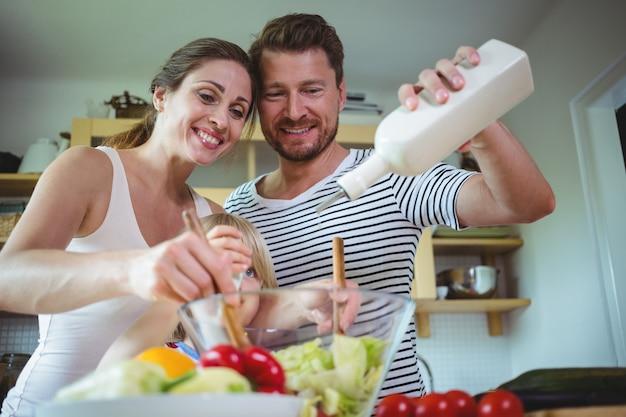 Família preparando salada na cozinha