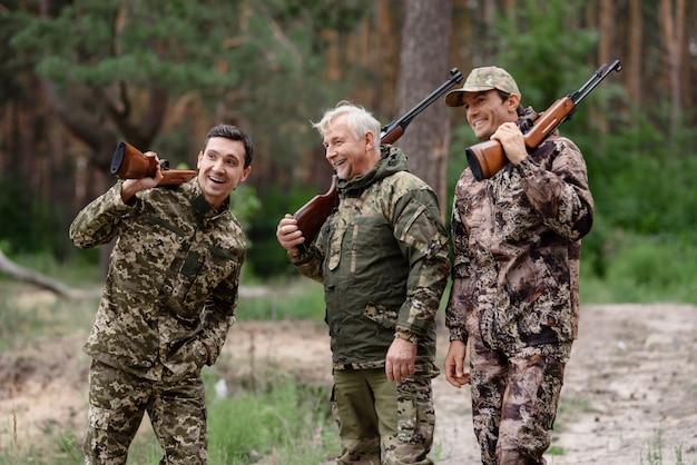 Família que caça homens felizes que falam e que riem.