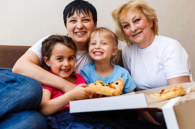 Família que come a refeição no restaurante ao ar livre junto pizza, rosa, azul