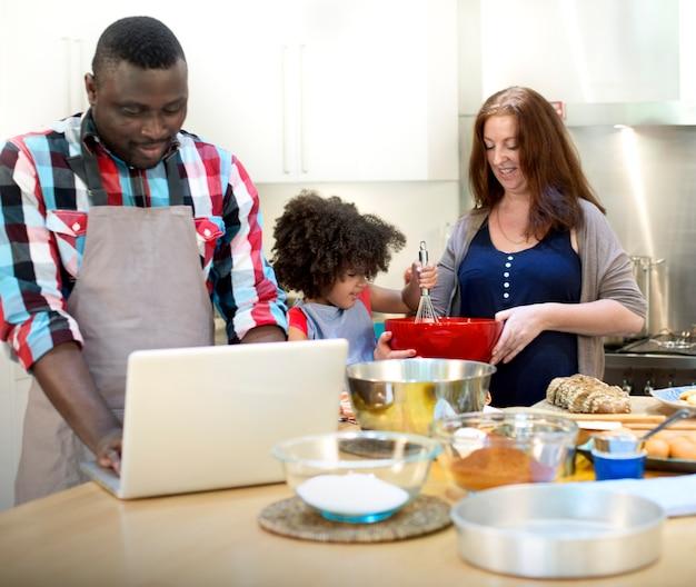 Família que cozinha o conceito da unidade do alimento da cozinha