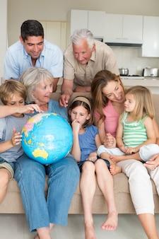 Família que explora o globo na sala de estar