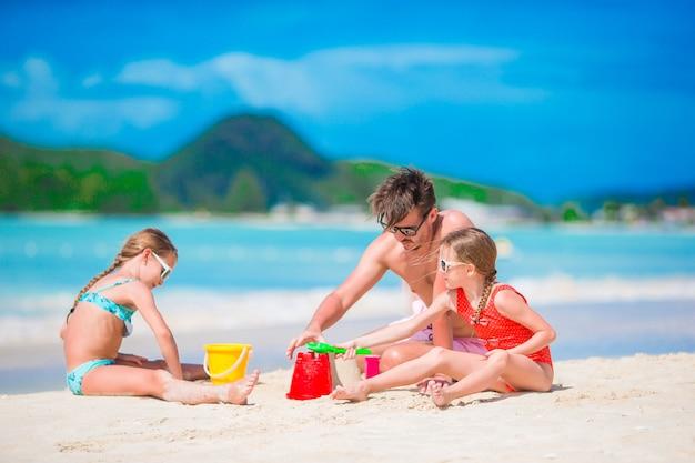 Família que faz o castelo da areia na praia branca tropical.