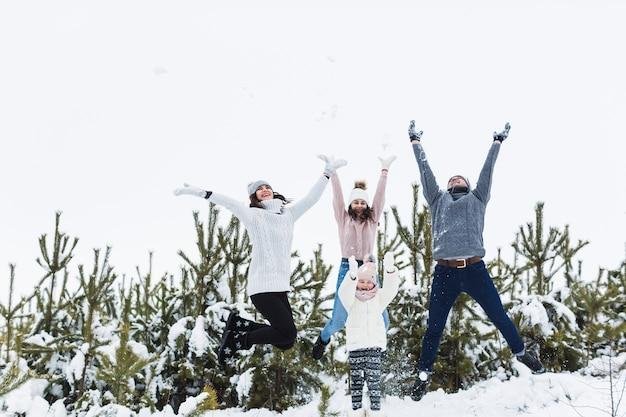 Família que salta na floresta do inverno