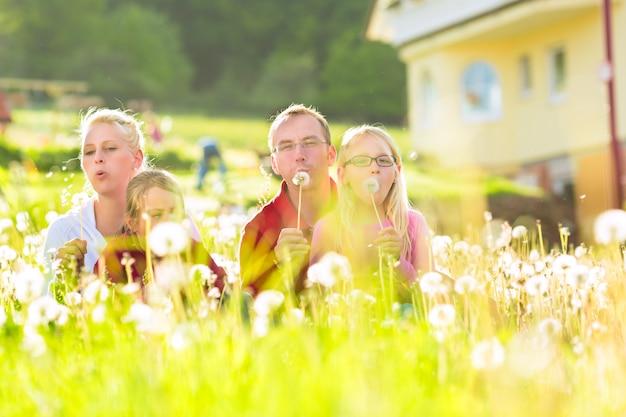 Família que senta-se no prado na frente da casa
