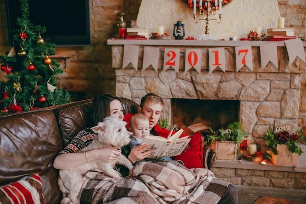 Família que sorri em um sofá com um livro nas mãos do pai e de um fundo lareira com o cartaz