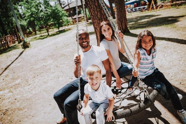 Família racial multi no parque africano no balanço da web