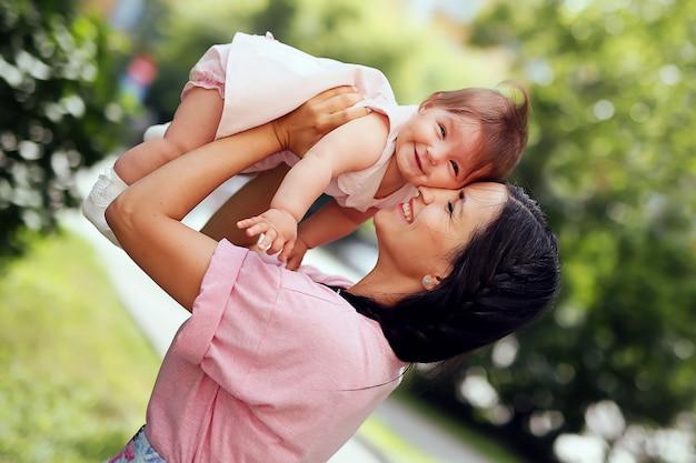 Família. retrato da mãe alegre bonita com sua filha bonito que tem o divertimento junto no parque.