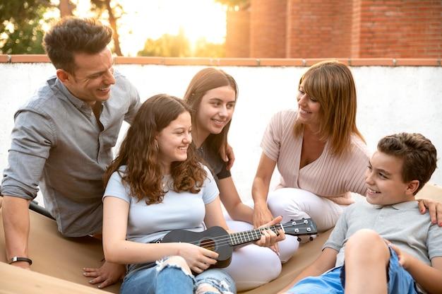 Família reunida e tocando ukulele