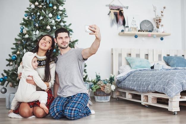 Família reunida em torno de uma árvore de natal fazendo uma selfie