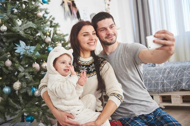Família reunida em torno de uma árvore de natal, usando um tablet