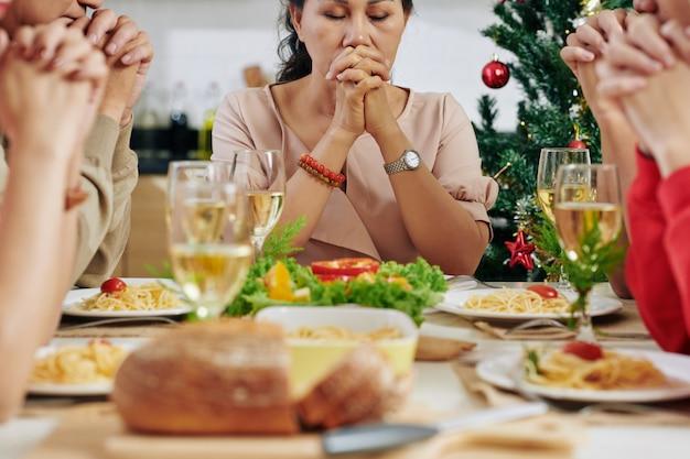 Família rezando na mesa de jantar