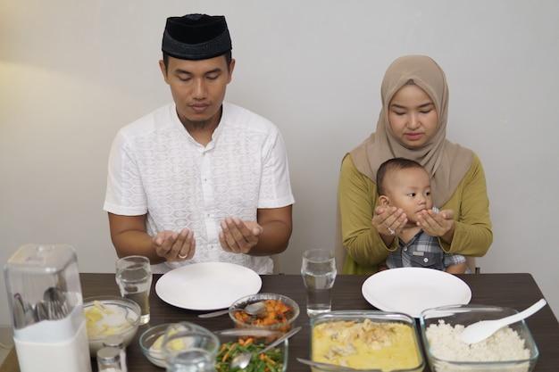 Família rezar antes de jantar juntos
