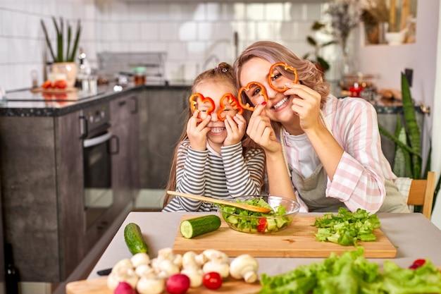 Família se diverte enquanto cozinha na cozinha, adorável mulher com criança esculpindo legumes frescos, sorria, aproveite o processo