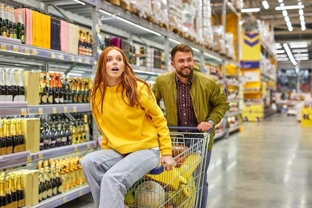Família se diverte no corredor do supermercado, mulher senta no carrinho e gosta de fazer compras com o marido. mulher surpresa viu algo interessante