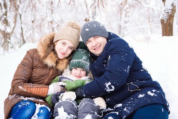 Família se divertindo, brincando no inverno a pé ao ar livre
