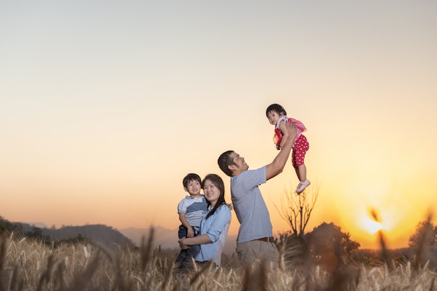 Família se divertindo e jogando em um campo de cevada em vez do sol.