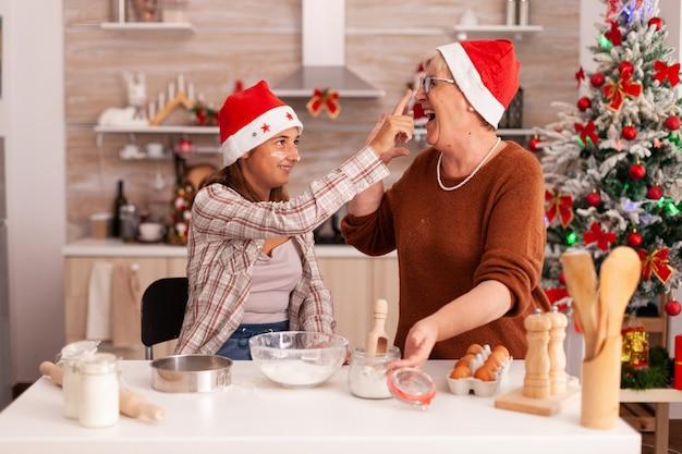 Família se divertindo junto brincando com farinha enquanto cozinham sobremesas caseiras
