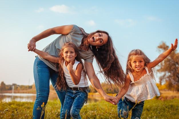 Família se divertindo pelo rio de verão ao pôr do sol, mãe rindo e fazendo careta com filhas