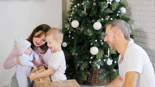 Família se divertindo perto da árvore de natal e presentes