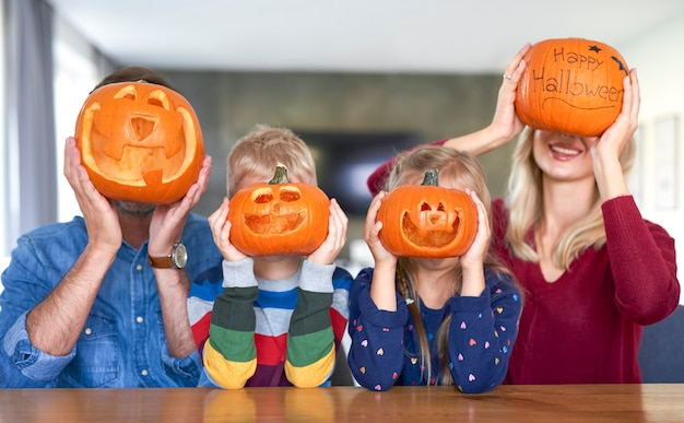 Família segurando abóboras de halloween na frente do rosto