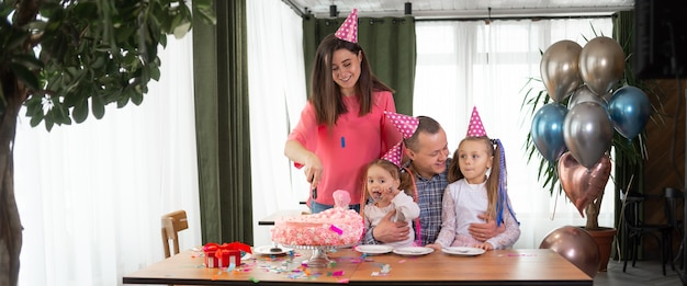 Família sentada à mesa e comemorando um aniversário. uma mulher está cortando um bolo em pedaços.
