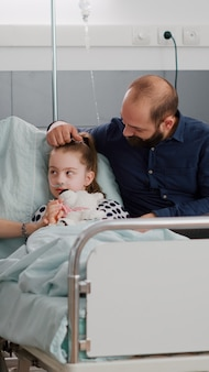Família sentada ao lado da filha doente hospitalizada discutindo tratamento de recuperação de medicação
