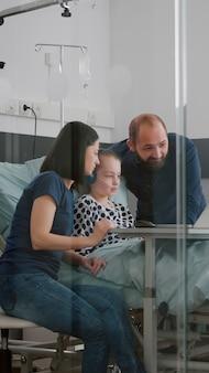 Família sentada com a filha doente na enfermaria do hospital durante o exame de doença, assistindo ao filme on-line de entretenimento de terapia usando o laptop. paciente do sexo feminino com tubo nasal de oxigênio relaxando após a cirurgia