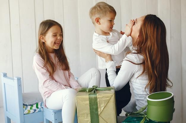 Família sentada em casa com presentes