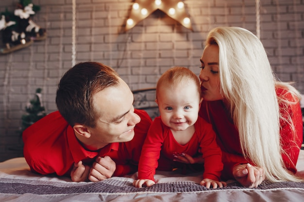 Família sentada em casa em uma cama