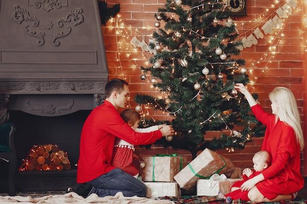 Família sentada em casa perto de árvore de natal