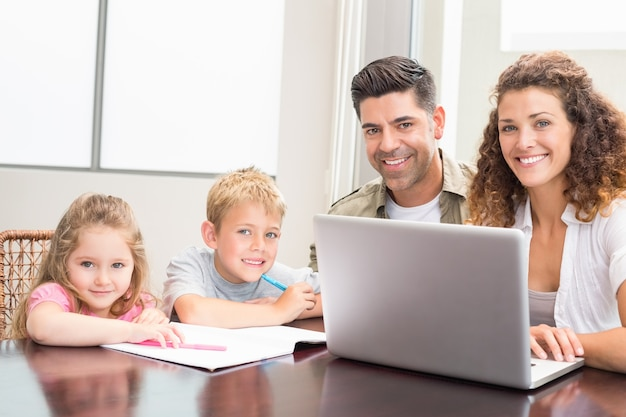 Família sentada em mesa com laptop e livro para colorir