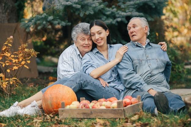 Família sentada em um jardim com maçãs e abóbora