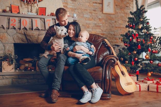 Família sentada em um sofá com o cão no natal