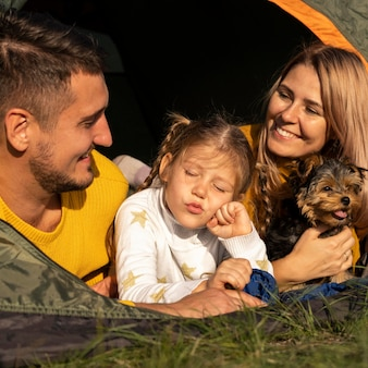 Família sentada em uma barraca com seu cachorro em close-up