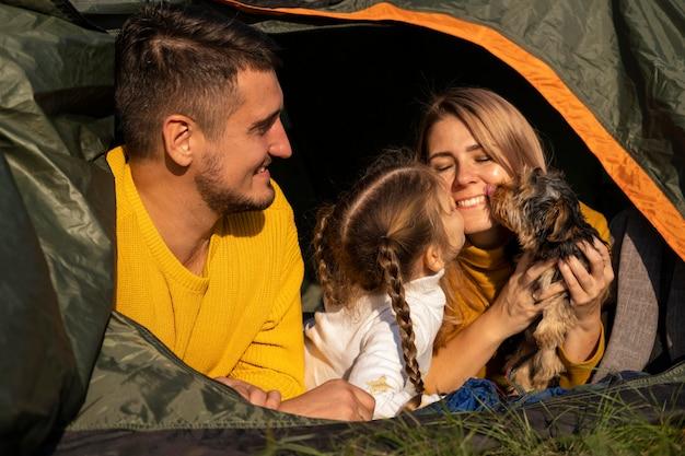 Família sentada em uma barraca com seu cachorro