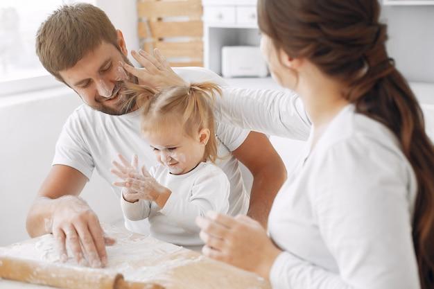 Família sentada em uma cozinha e cozinhar a massa para biscoitos