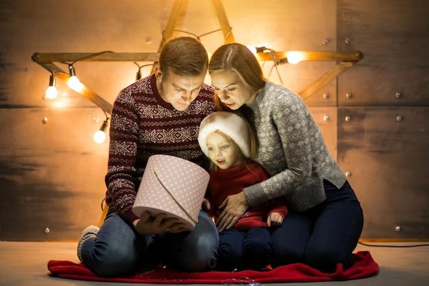 Família sentada junto à árvore de natal com presentes de embalagem da filha pequena
