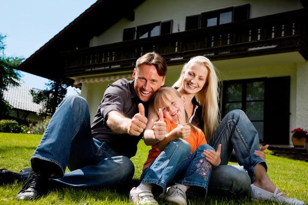Família sentada na frente de sua casa