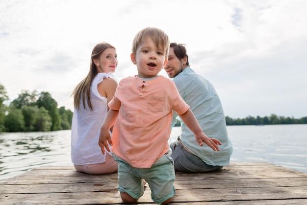 Família sentada no cais da lagoa ou lago no verão