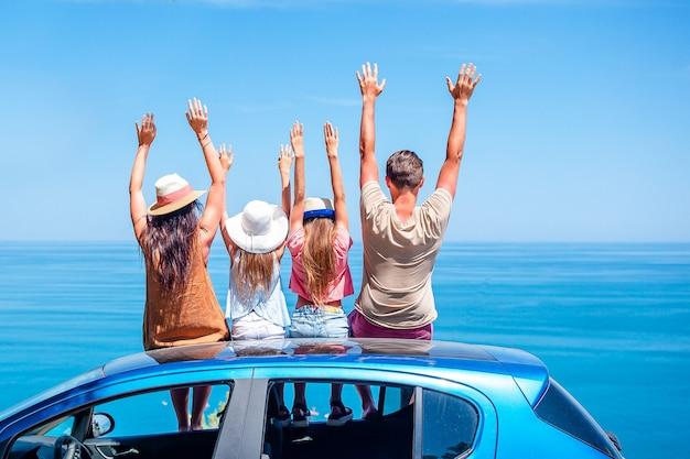 Família sentada no carro em frente ao mar