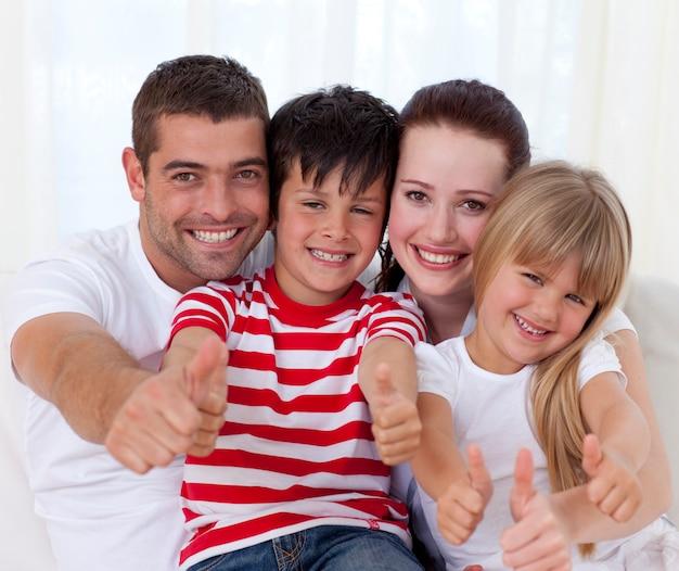 Família sentada no sofá com polegares para cima