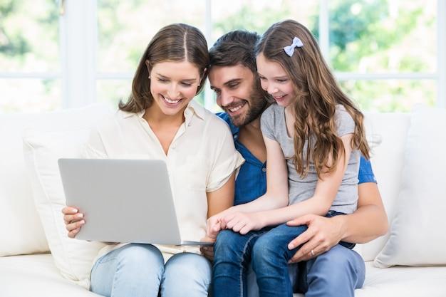 Família sentada no sofá e olhando para laptop